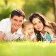 Happy mother, father and daughter in the park — Stock Photo #18047961