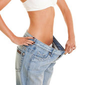 Woman shows her weight loss by wearing an old jeans, isolated o — Stock Photo