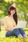 Cute kobietę w słuchawki z białym laptopa w parku — Zdjęcie stockowe