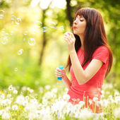 Happy woman blowing bubbles in the park — Stock Photo