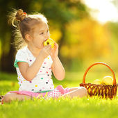 Cute little girl eating apple in the park — Stock Photo