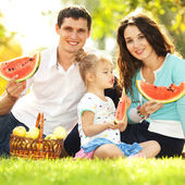 Happy family having a picnic in the green garden — Stock Photo