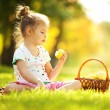 Cute little girl eating apple in the park — Stock Photo #18333791