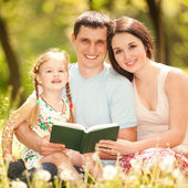 Happy mother, father and daughter read a book in the park — Stok fotoğraf