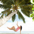 Happy woman relaxing in hammock on a tropical beach — Stock Photo #19560899