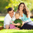 Happy family having a picnic in the green garden — Stock Photo #19561039