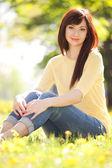Ung kvinna i parken med blommor — Stockfoto