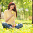 Happy woman eating fruits in the park — Stock Photo