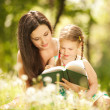 Mother with daughter read a book in the park — Stock Photo #21942571