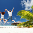Happy couple jumping in the tropical beach — Stock Photo #21942717