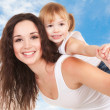 Happy mother and daughter playing on sky background — Stock Photo #21942849