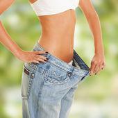 Eski kot giyerek, kadın onu kilo kaybı gösterir — Stok fotoğraf