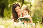 Mother with daughter read a book in the park — Stock fotografie