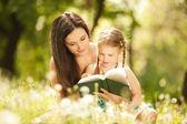Mère et fille lire un livre dans le parc — Photo