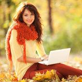 Ładny kobieta z białym laptopa w parku jesień — Zdjęcie stockowe