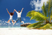 Happy couple jumping in the tropical beach — Stok fotoğraf