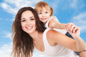 Happy mother and daughter playing on sky background — Stock Photo