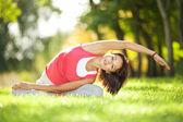 Bella donna facendo esercizi di yoga nel parco — Foto Stock