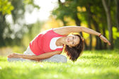 Mooie vrouw doen yoga oefeningen in het park — Stockfoto