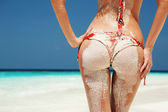 Sexy sandy woman buttocks on the beach background — Stock Photo