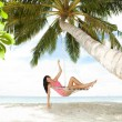Happy woman relaxing in hammock on a tropical beach - Foto Stock