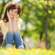 Young woman in the park with flowers — Stock Photo #22746275