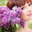 Young woman with lilac flowers — Stock Photo #22746299