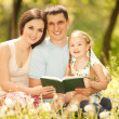 Stock Photo: Happy mother, father and daughter read a book in the park