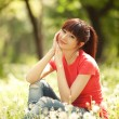 Cute woman in the park with dandelions - Foto Stock