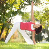 Pretty woman doing yoga exercises in the park — Stock Photo
