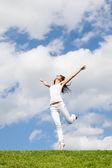 Ganska ung kvinna hoppa på grönt gräs — Stockfoto