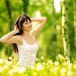 Cute woman in the park with dandelions — Stock Photo