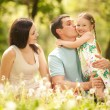 Happy mother, father and daughter in the park — Stock Photo #22879534
