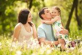 счастливая мать, отец и дочь в парке — Стоковое фото