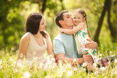 Happy mother, father and daughter in the park — Stok fotoğraf