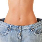 Mujer muestra su pérdida de peso usando un viejo jeans, aislada en — Foto de Stock
