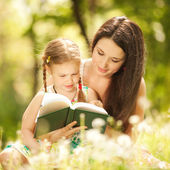 Mother with daughter read a book in the park — Stok fotoğraf