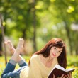 Young woman reading a book in the park with flowers — Stock Photo #23893363