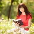 Young woman reading a book in the park with flowers — Stock Photo #23893375