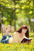 Young woman reading a book in the park with flowers — Stock Photo
