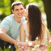 Happy couple kissing in the park — Stock Photo