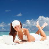 Roztomilá žena s bílým laptop na letní beach — Stock fotografie
