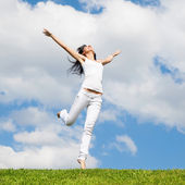 Joven y guapa mujer saltando sobre la hierba verde — Foto de Stock