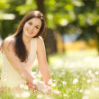 Cute woman rest in the park with dandelions — Stock Photo #24163975