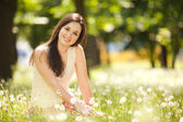Cute woman rest in the park with dandelions — Stockfoto