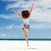 Happy young woman jumping on the beach — Stok fotoğraf
