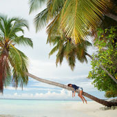Happy woman lying upon palm tree on the beach — Stock Photo