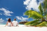 Happy couple sitting on the sunny beach — Stok fotoğraf