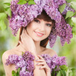 Stock Photo: Young woman with lilac flowers