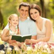 Happy mother, father and daughter read a book in the park — Stock Photo